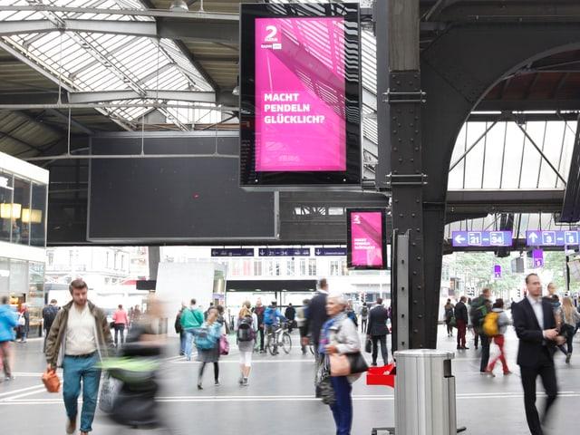 Bahnhofshalle Zürich, Pendler - oben auf der Werbetafel die Frage: Macht pendeln glücklich?