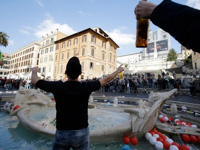 Wild gestikulierende Fussballfans mit Bierflaschen in der Hand stehen in und um den Brunnen.