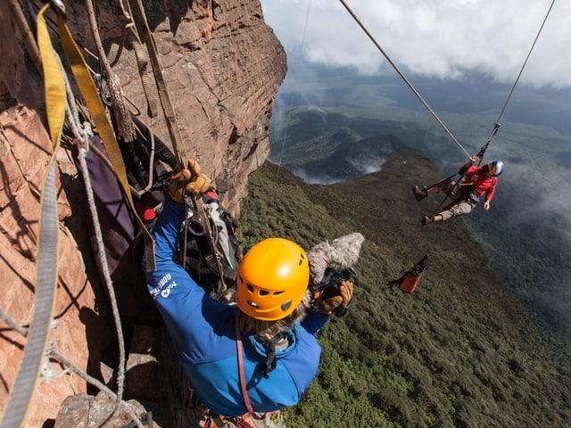 Ein Kletterer filmt an der Felswand, der andere hängt in der Luft.