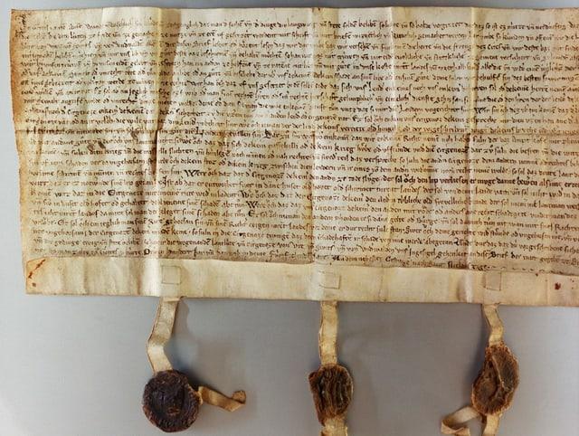 Ein dicht beschriebenes gelbliches papier mit den drei Siegeln am unteren Ende.