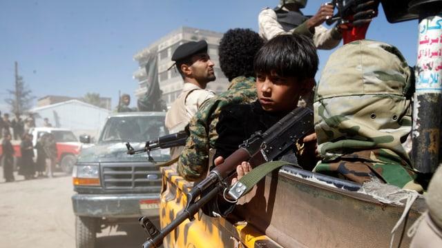 Männer und Jungen mit Gewehren auf einem Pick-Up-Truck.