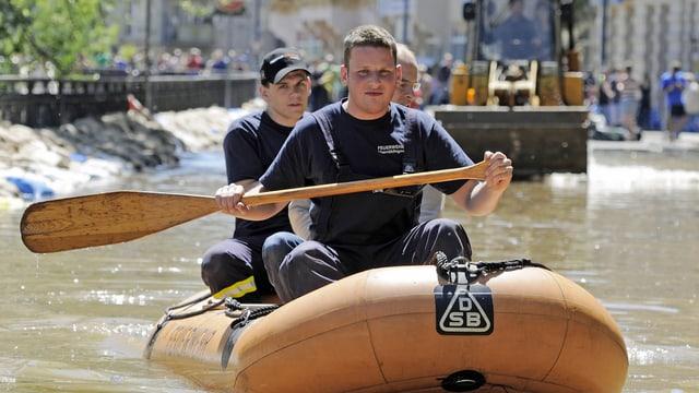 Feuerwehrmänner paddeln durch einen überfluteten Stadtteil von Halle. (keystone)
