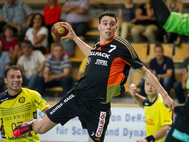 Florian Goepfert wirft den Ball gleich zwischen zwei Gegenern durch.