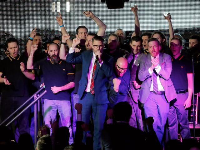 Gavin McInnes steht auf der Bühne, umgeben von jungen, weissen Männern.