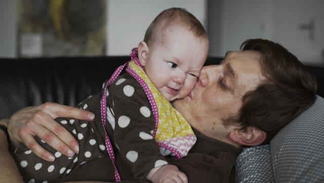 Ein Mann mit einem Baby auf der Brust.