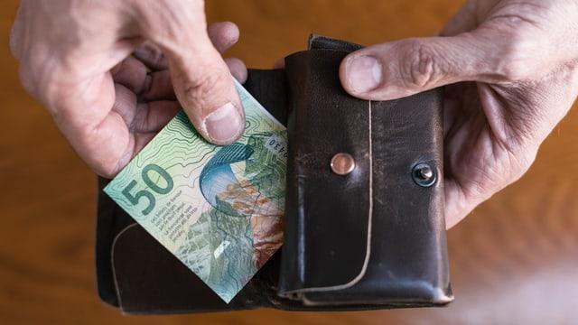 Hand zieht Banknote aus Geldbeute.