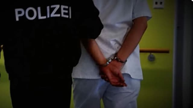 """Ein Polizist verhaftet den Todespfleger (Szene aus dem SRF-Film """"Der Todespfleger aus der Innerschweiz"""")"""