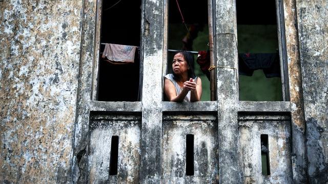 Eine burmesische Frau schaut aus einem Fenster ohne Scheiben.