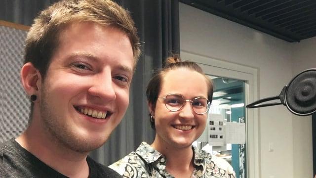 Zwei junge Menschen in einem Radiostudio schauen lachend in die Kamera
