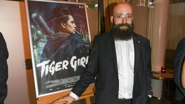 """Der Regisseur Jakob Lass steht vor dem Filmplakat von """"Tiger Girl""""."""