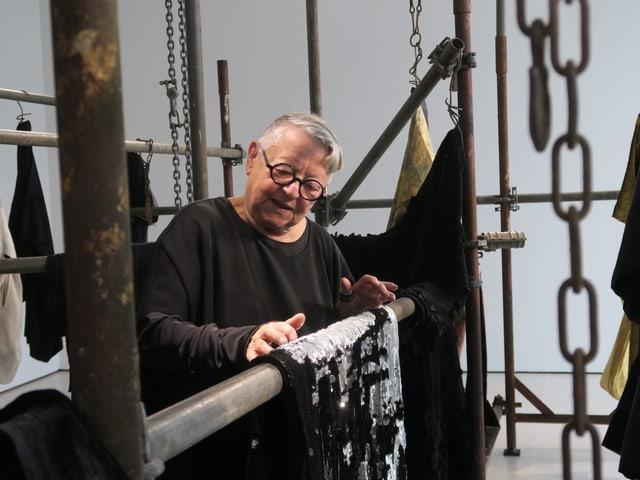 Eine ältere Frau mit Tüchern bei einer Stange.