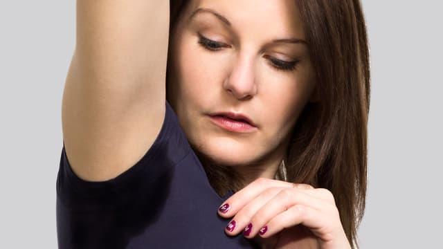 Eine Frau betrachtet einen dunkeln Schweissfleck auf ihrem T-Shirt.