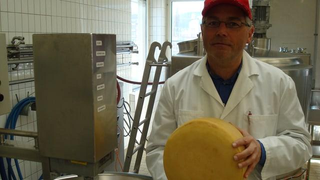 Ein Mann im Laborkittel mit einem Käse.