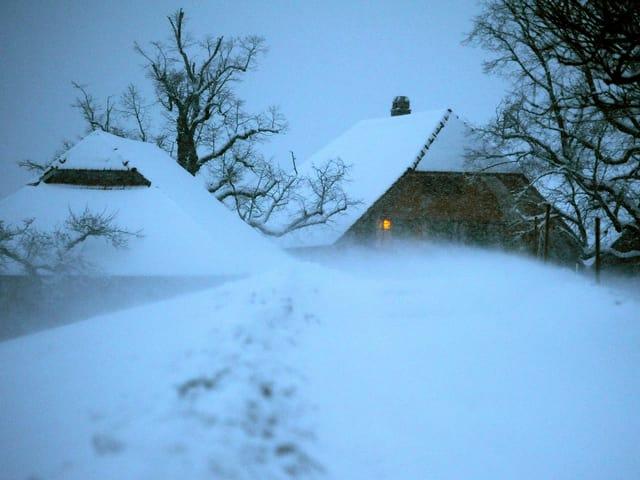Zwei Bauernhäuser tief im Schnee. In einem Fenster leuchtet ein kleines Licht.
