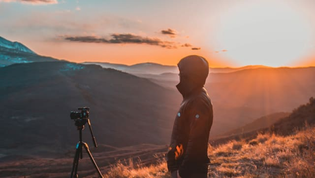 Sonnenaufgang mit Kamera und Mann um Vordergrund
