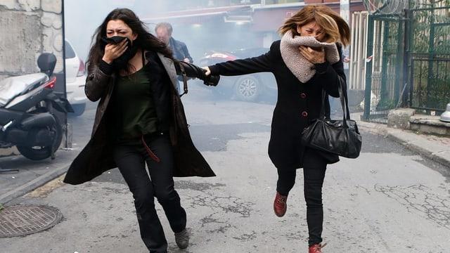 Duas dunnas fugian dal gas lacrimogen.