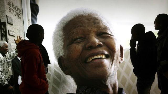Ein grosses Bild vom lachenden Nelson Mandela, begutachtet von Kunstinteressierten.