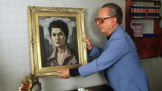 ein älterer Mann hängt ein Porträt einer Frau auf