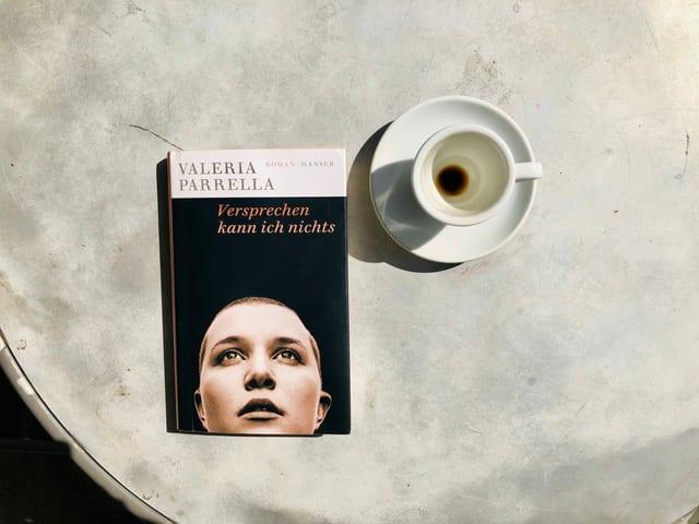 Der Roman «Versprechen kann ich nichts» von Valeria Parrella liegt auf einem Bistrotisch. Daneben steht eine leergetrunkene Espressotasse.