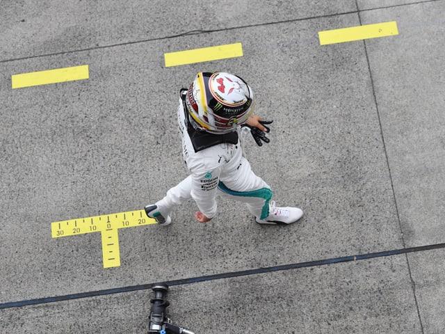 Lewis Hamilton rennt über den Asphalt.