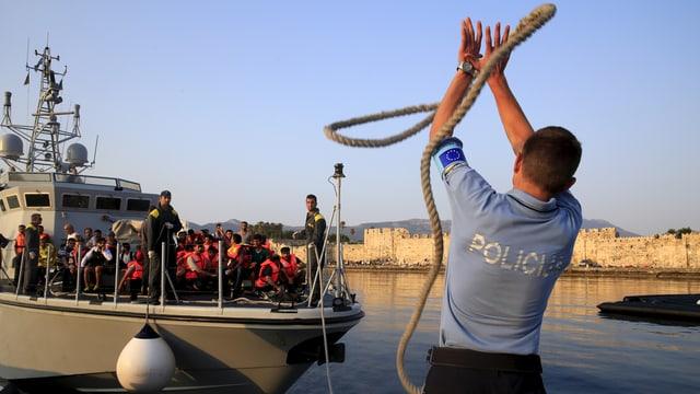 Ein Polizist wirft ein Seil zu einem Küstenwache-Boot voller Flüchtlinge.