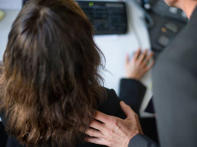 Ein Mann legt die Hand auf die Schulter einer Arbeitskollegin