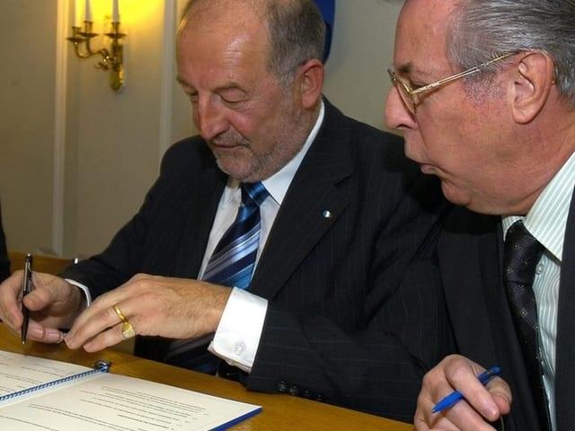 Die beiden Männer unterzeichnen den Vertrag.