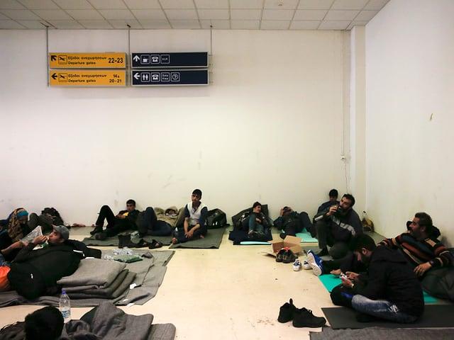 Flüchtlinge sitzen am Boden auf dünnen Matten in einer Halle des alten Athener Flughafens.