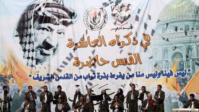 Eine Musik-Band aus mehreren Mitgliedern bestehend spielt vor dem Hintergrund eines Arafat-Porträts