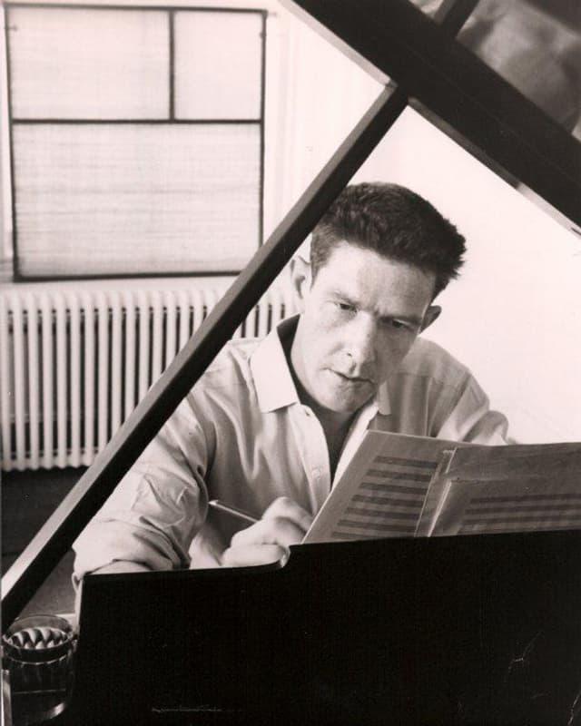 John Cage in jungen Jahren, an einer Komposition arbeitend an seinem Klavier.