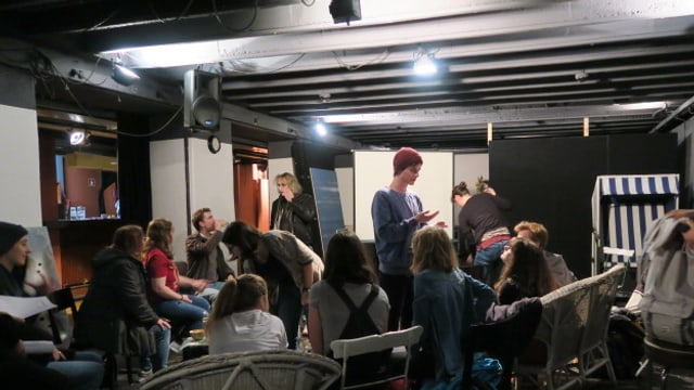Jugendliche sitzend und stehend in einem Raum.