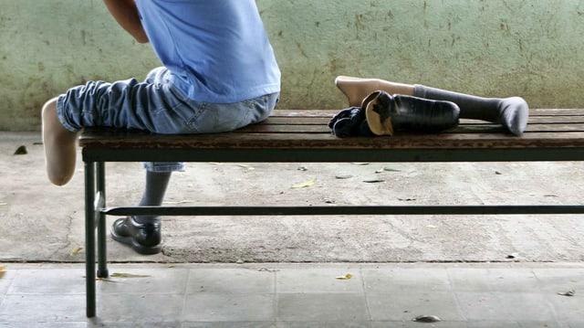 Beinamputierte Person auf einer Bank.