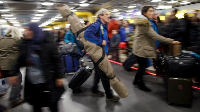 Touristen mit Skisäcken und Rollkoffern ziehen ihr Gepäck über den Genfer Flughafen.