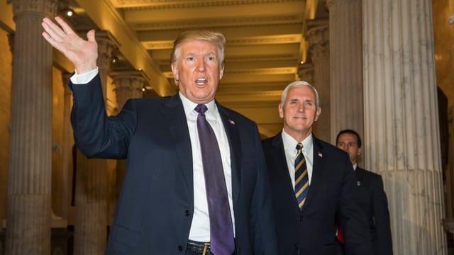 Donald Trump links winkt beim Verlassen des Capitols, recht sein Vize Mike Pence.