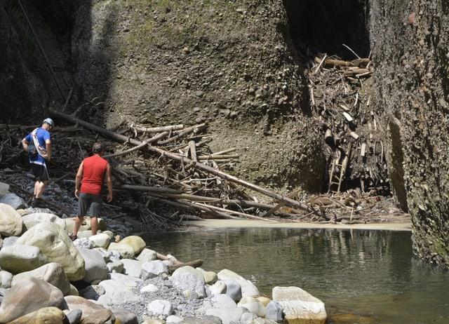 2 Männer stehen in einer engen Schlucht. Sie blicken auf einen Berg von Holz.