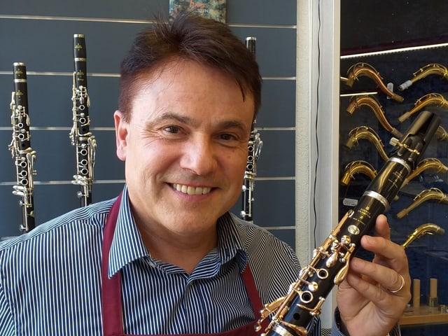Ein Mann mit einer Klarinette vor einem Gestell mit Klarinetten.