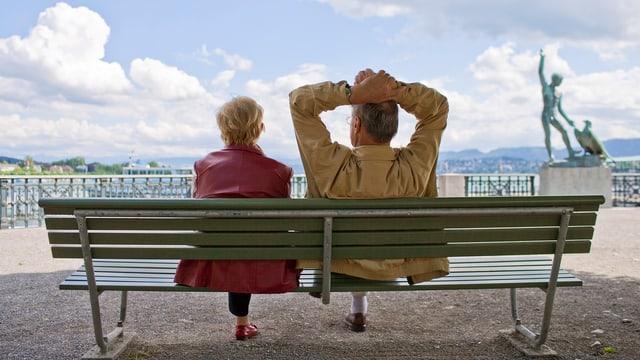 Ein älteres Paar sitzt auf einer Parkbank und schaut in die Ferne.