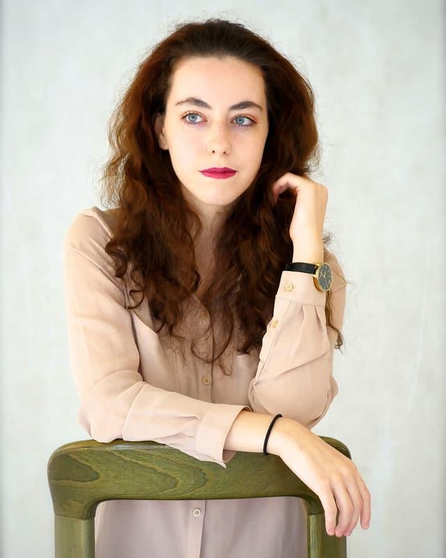 Eine junge Frau mit langem Haar stützt sich auf die grüne Lehne eines Stuhls.