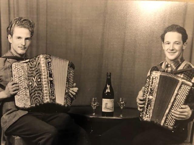 Zwei junge Akkordeonisten an einem Tisch.