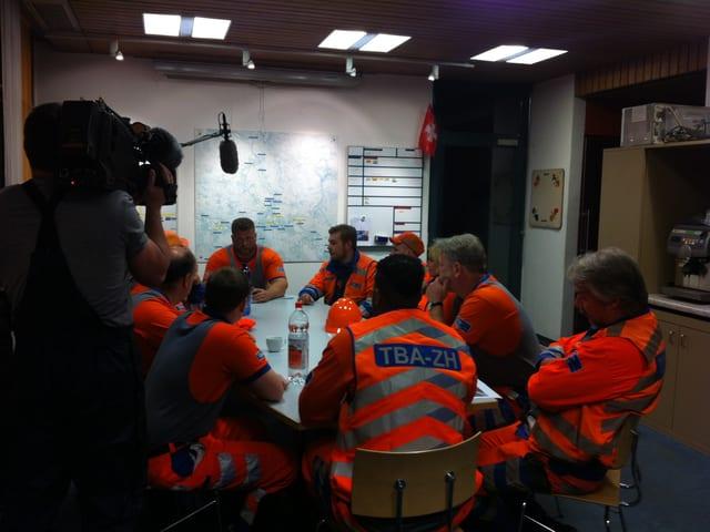 Männer sitzen für ein Briefing des Einsatzes um einen Tisch.
