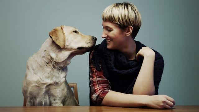 Eine Frau und ein Hund sitzen an einem Tisch und schauen sich freundlich an.