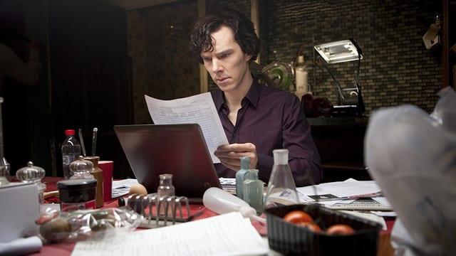 Sherlock liest an einem chaotischen Tisch handgeschriebene Dokumente.