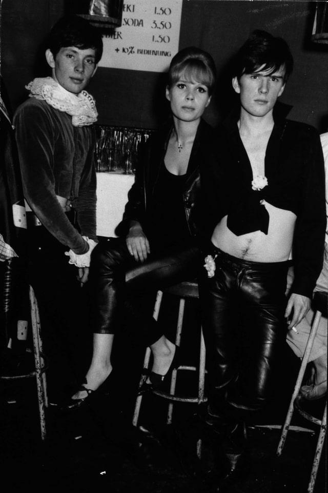 Klaus Voorman mit Astrid Kirchherr und Stu Sutcliff auf Barhockern.