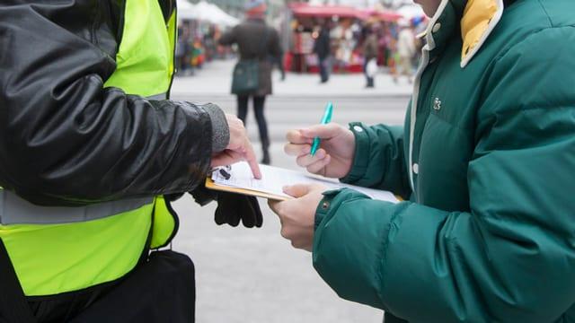 Ein Herr sammelt auf der Strasse Unterschriften, eine Frau unterschreibt einen Papierbogen.