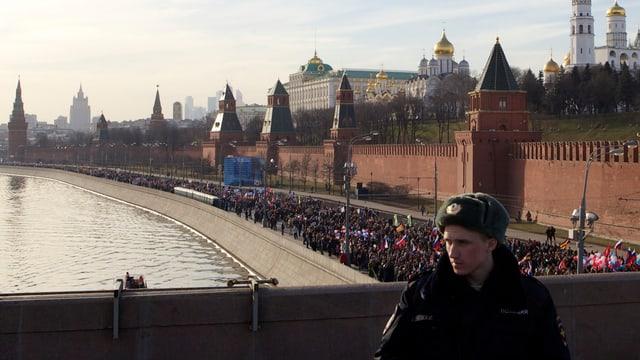 Ein Soldat, im Hintergrund die Mauern des Kremls und eine Kundgebung zum Jahrestag der Heimholung der Krim