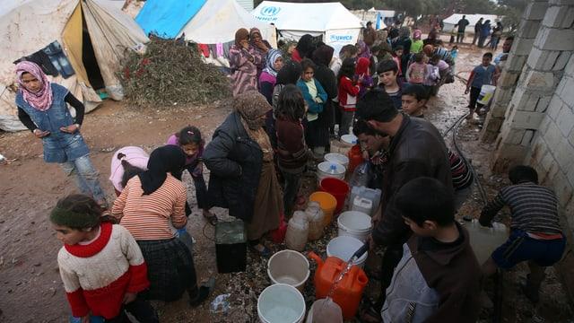 Syrische Flüchtlinge stehen in einem Flüchtlingslager um zahlreiche Behälter.