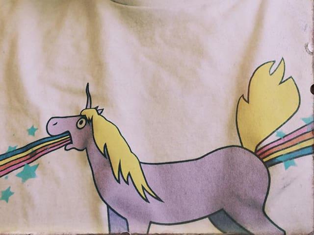Einhorn auf T-Shirt kotzt Regenbogen.