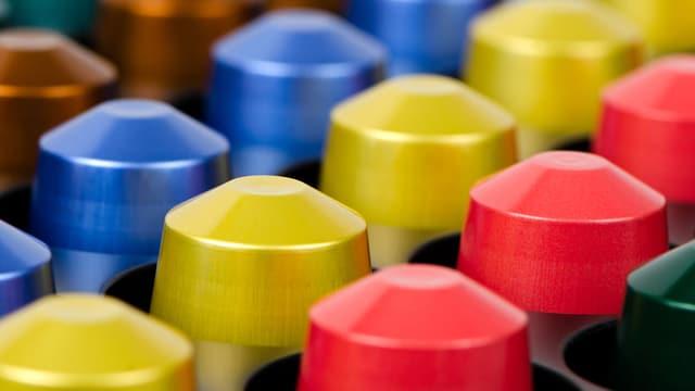 verschiedenfarbige Kaffeekapseln nach Farbe sortiert aufgereiht.