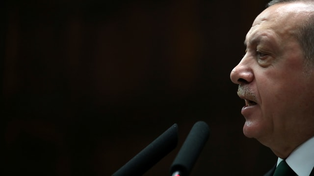 Erdogan spricht vor schwarzem Hintergrund in ein Mikrofon.