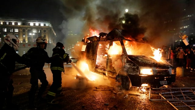 Die Feuerwehr versucht in der Nacht, ein brennendes Auto zu löschen.